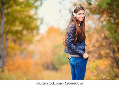 A portrait of a beautiful young woman walking in an autumn forest and listening to music. Lifestyle, autumn fashion, beauty.