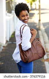 Portrait of a beautiful young woman walking along a street with a purse and looking over her shoulder
