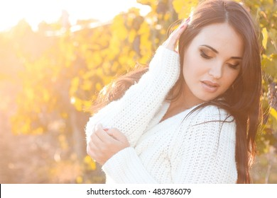 Portrait of a beautiful young woman in the warm sunshine. Autumn portrait of a young woman in a warm knitted sweater. Warm autumn.