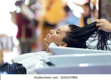 Portrait of beautiful young woman washes hair in a beauty salon.