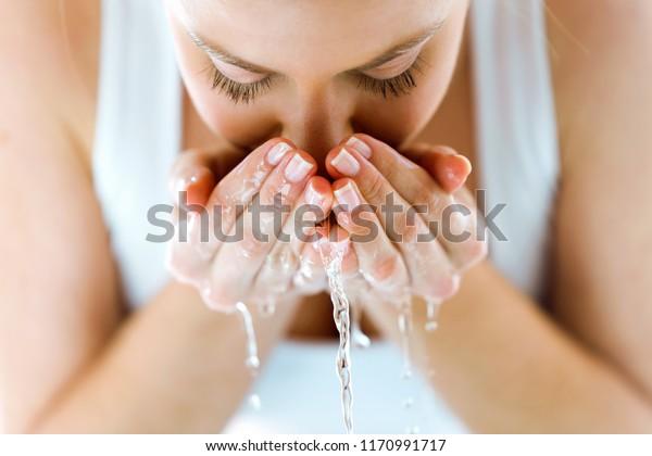 家庭用トイレで水を跳ねながら顔を洗う美しい若い女性のポートレート。