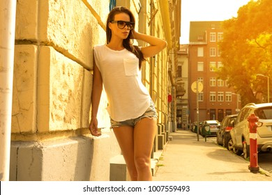 Portrait of a beautiful young woman wearing Jeans Hotpants posing in a European urban environment.
