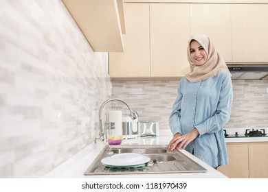 portrait of beautiful young woman wearing hijab washing the dishes