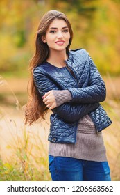 A portrait of a beautiful young woman wearing a leather jacket in an autumn forest. Lifestyle, autumn fashion, beauty.