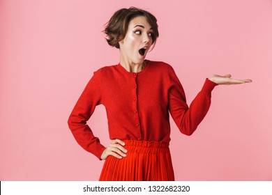 Portrait of a beautiful young woman wearing red clothes standing isolated over pink background, presenting copy space
