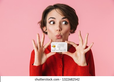 Portrait of a beautiful young woman wearing red clothes standing isolated over pink background, holding credit card