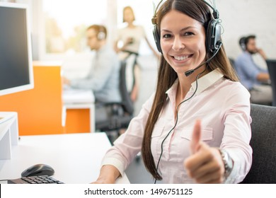 Portrait of beautiful young woman wearing headset showing thumbs up gesture. Customer support service agent woman working in call center and showing success sign with a hand.