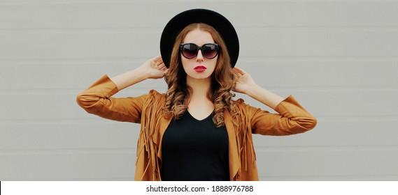 Portrait einer schönen jungen Frau mit einem schwarzen, runden Hut, brauner Jacke auf grauem Hintergrund