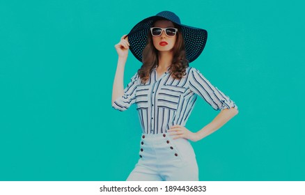 Portrait of beautiful young woman wearing a black round summer hat, white striped shirt on a blue background