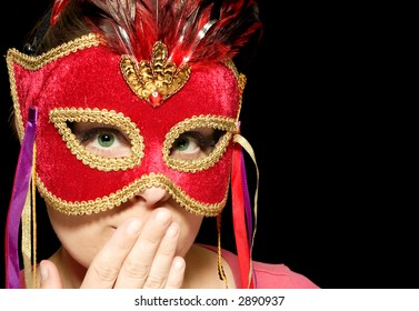 Portrait of a beautiful young woman wearing carnival mask surprised and shocked