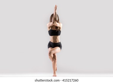Portrait of beautiful young woman wearing black sportswear working out in studio. Fit sporty girl doing advanced yoga, pilates, fitness. Eagle Pose, Garudasana. Full length