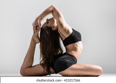 Portrait of beautiful young woman wearing black sportswear working out in studio. Fit sporty girl stretching with closed eyes. Eka Pada Rajakapotasana Pose, One-Legged King Pigeon Posture. Side view