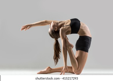 Portrait of beautiful young woman wearing black sportswear working out in studio. Fit sporty girl doing advanced yoga, pilates, fitness. Stretching with closed eyes. Ustrasana, Camel Posture