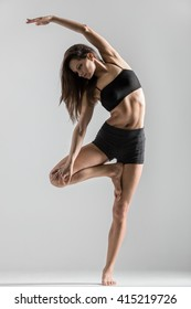 Portrait of beautiful young woman wearing black sportswear working out in studio. Fit sporty girl doing side bend exercise. Variation of Vrksasana Posture, Tree Pose. Full length. Vertical image