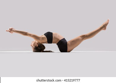 Portrait of beautiful young woman wearing black sportswear working out in studio. Fit sporty girl doing advanced yoga, pilates, fitness. Matsyasana, Fish pose with lifted legs. Side view image