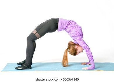 Portrait of beautiful young woman wearing sportswear working out in studio. Fit sporty girl doing backbend exercise. Camatkarasana, Wild Thing or Flip-the-Dog posture. Full length. Side view.