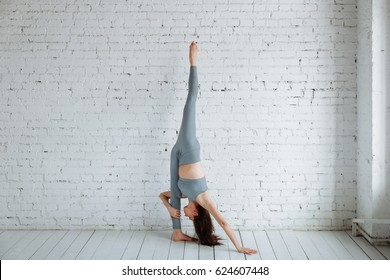 Portrait of a beautiful young woman wearing grey clothes works against white walls, doing yoga or Pilates exercises. Handstand with splits, the change in Pincha Mayurasana. Full length shot