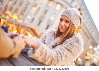 Portrait of a beautiful young woman while sitting in a christmas market and holding her boyfriends hand.