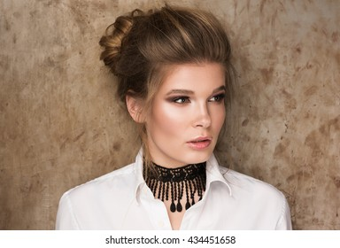 Portrait of a beautiful young woman in a white shirt with a black choker on her neck. Professional Nude-makeup. Perfect clean skin. Hair in a bun. Metal wall in the background