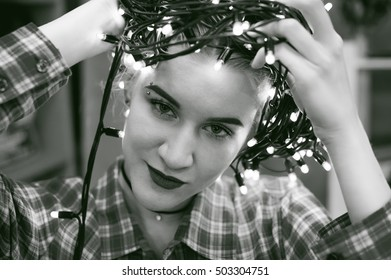 portrait of a beautiful young woman who wears on his head the Christmas lights, instead of a hat