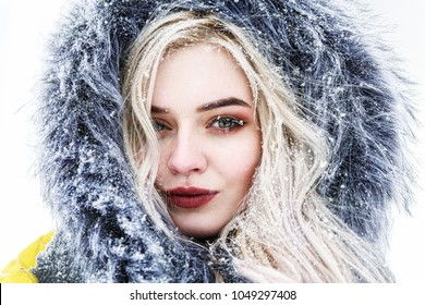Portrait of a beautiful young woman in a winter blizzard. The blizzard is blinking. Snowing. Close-up portrait of a blonde woman.