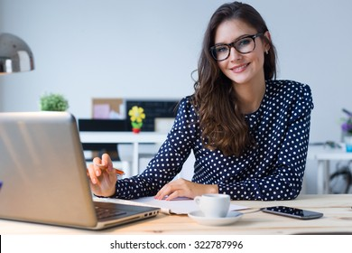 Portrait of beautiful young woman working with laptop in her office.