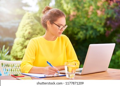 Portrait of beautiful young woman writing something and using her laptop while sitting outdoors.
