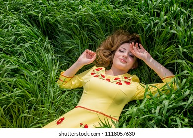 Portrait of the beautiful young woman in a beautiful yellow sundress lying in a high juicy grass
