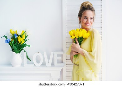 Portrait of a beautiful young woman in yellow dress with spring flowers and white decoration letters