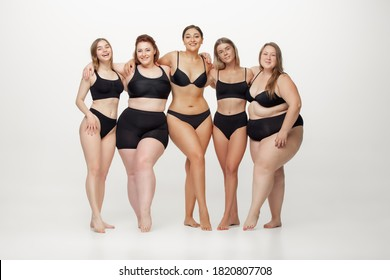 Portrait of beautiful young women with different shapes posing on white background. Happy female models. Concept of body positive, beauty, fashion, style, feminism. Diversity.