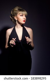 Portrait of beautiful young women exists blonde with bright makeup. Girl dressed in black evening dress on a black background.