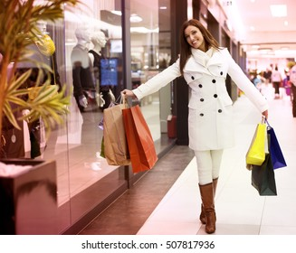 Portrait of beautifull young girl with shopping bags walking out from shop
