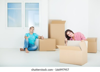Portrait of beautiful,smiling woman sitting with man while unpacking cardboard boxes in new home
