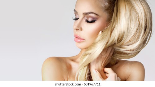Portrait beauty blonde female model with amazing long  hair and perfect face clean young skin care posing on a white background