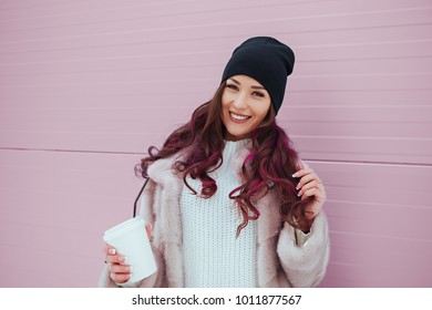 Portrait of beauty fashion smiling woman with coffee in mink coat and black hat on pink background. Outdoor