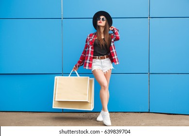 Portrait of beauty fashion smiling woman with shopping bags in sunglasses on blue background. Outdoor. Copyspace