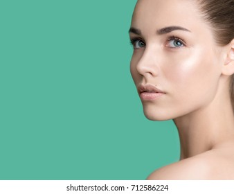 Portrait of beauty model with clean perfect skin  looking up. Spa, skincare and wellness. Beautiful young woman with natural nude make up and long eyelashes. Light green background, copyspace.