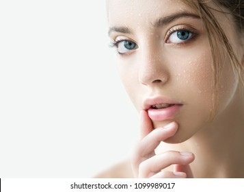 Portrait of beauty model with natural nude makeup moisturizing her skin. Spa, skincare and wellness. Beautiful young woman with clean perfect skin and water moisture drops. Close up.