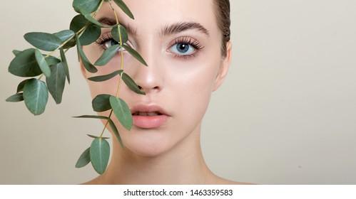 Porträt des Schönheitsmodells mit natürlichem Aktbild mit Eukalyptusblattzweig.  Schöne junge Frau mit sauberer, perfekter Haut. Spa-, Skincare- und Wellness-Konzept. Nahaufnahme.