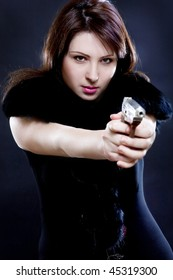 portrait of beauty with the pistol on black background