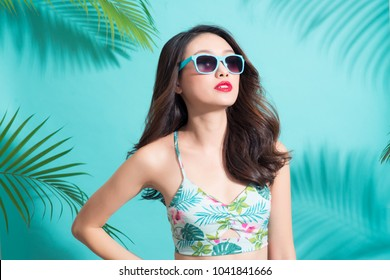 Portrait beauty sexy asian model with perfect face wearing a sunglasses and elegant bikini on palm tree shadow background.