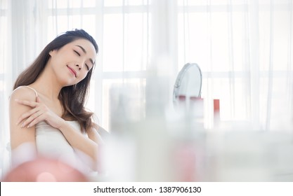 Portrait of beauty smiling asian woman applying a lotion to her arm skin during her morning routine. Skincare body lotion, beauty clinic skincare spa indoors, asia girl lifestyle concept