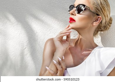 Portrait beauty stunning sexy blonde model  with perfect face wearing a sunglasses and elegant white bikini on amazing view with palm tree shadow in Cannes, France