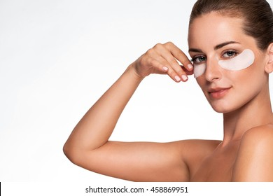 Portrait of Beauty woman with eye patches showing an effect of perfect skin. Beautiful face of young adult woman with clean fresh skin and bare shoulders on white background. Brunette Spa Girl.