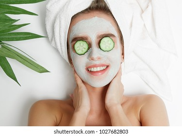 Portrait of beauty woman laying with towel on the head, cucumber on her eyes,facial mask. Spa therapy. Relax.
