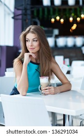 Portrait of a beauty young woman posing in a coffe shop