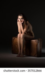 Portrait of beautyful naked posing blond woman sitting on leather suitcase, with long curly hair on black background