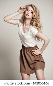 Portrait of beautyful posing blond woman with long curly hair on white background