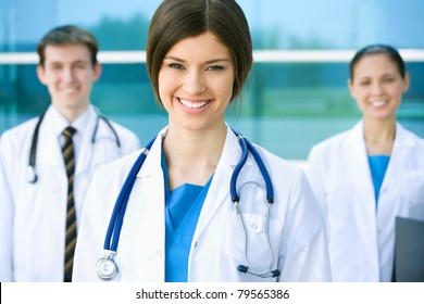 Portrait of a beautyful young female doctor standing in front of his team and smiling
