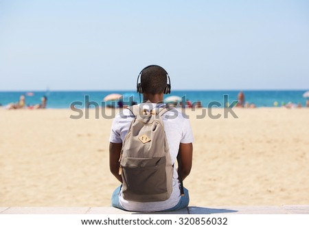 Portrait from behind of a young man sitting by the beach listening to music on headphones